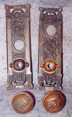 Turn of the century bronze door plates. Cleaned and polished, light patina in background.